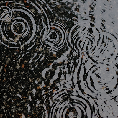 rain falling into a puddle causing ripples